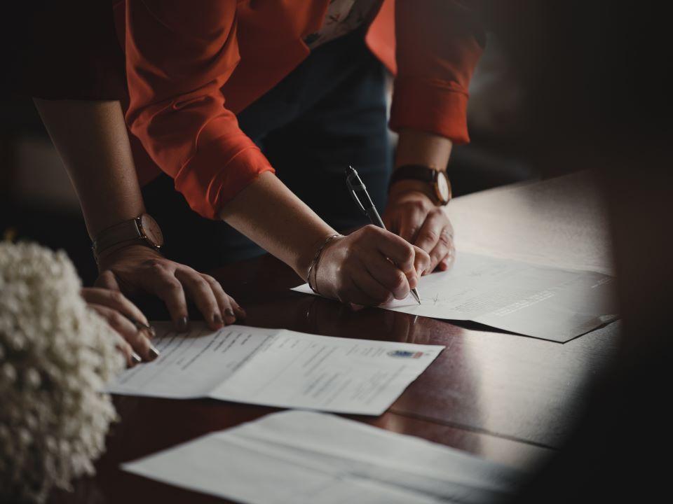 paveikslėlyje vaizduojamos rankos, kurios pasirašo sutartį
